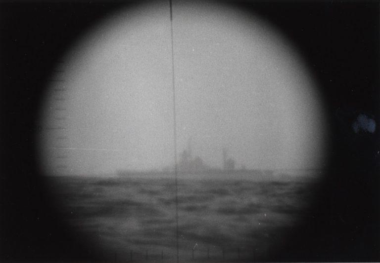 """Uidentificeret krigsskib - sandsynligvis en sovjetisk krydser af SVERDLOV-klassen - fotograferet gennem periskopet på ubåden S320 NARHVALEN af NARHVALEN-klassen. Med tekst: """"Patrulje 15"""". 29. marts 1976."""""""